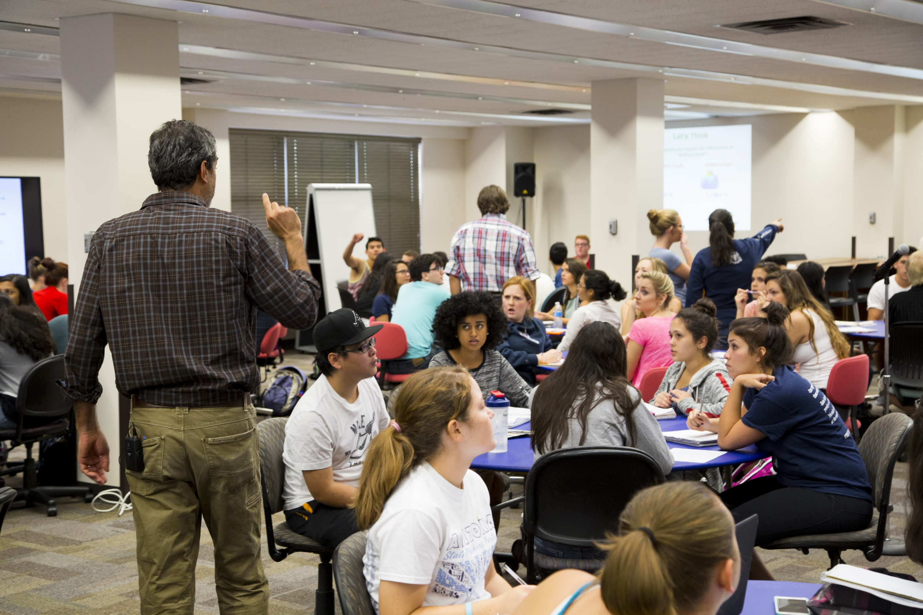 Instructor standing among students working in groups at several tables