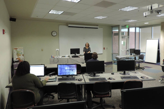Woman standing at instructor station with students seated at PC computer workstations