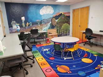 room with wall mural, tables, chairs, and a multi-color rug