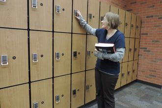 Woman holding books trying to unlock a lock in front of three rows of lockers