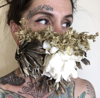 Women wearing a face mask of dried flowers