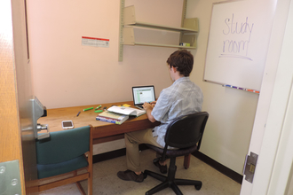 Graduate student sitting at small desk using laptop, with whiteboard on wall