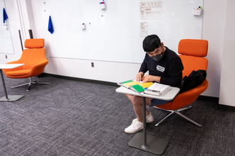 student reading in a comfortable chair