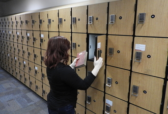 woman placing a book in a locker