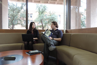 Man and woman seated on comfortable couch chatting near windows of Scholar's Corner