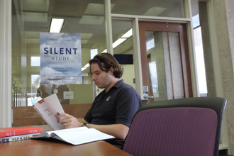 Man reading at a desk with sign for Silent Study Room in the background