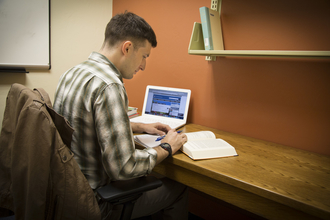 student with book and laptop in a private study room