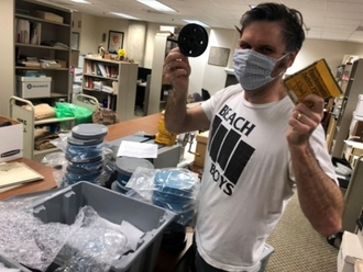 trent purdy holding up preserved films in both hands