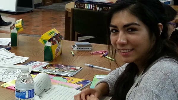 Student with crayons and coloring books