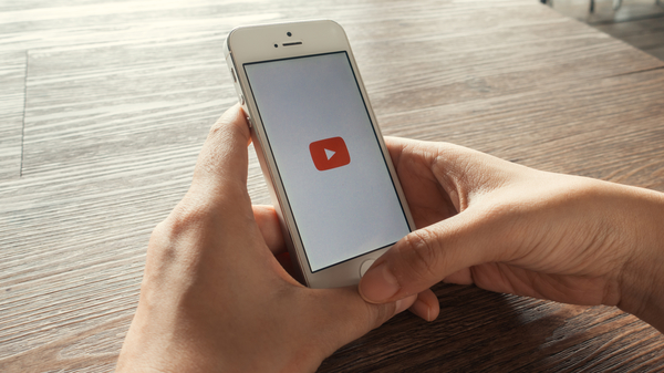 Holding a smartphone with YouTube logo on screen