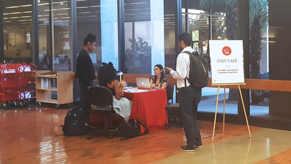 Students at a table talking with a library employee