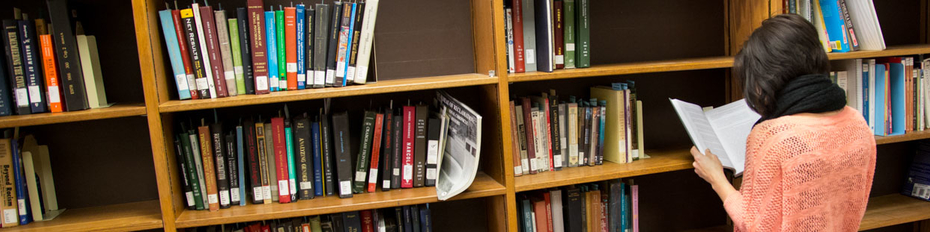 Woman looking at book from the hold shelf