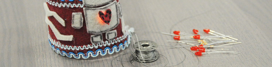 Photo showing a wearable bracelet designed with a felt robot and light up red heart, plus thread and pins