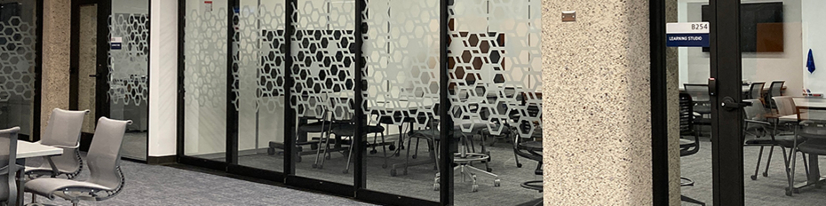 Learning Studio meeting room with hexagon graphic on the glass walls and chairs in the background