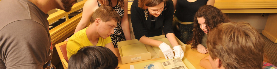 An instructor wearing white gloves shows primary source material to students