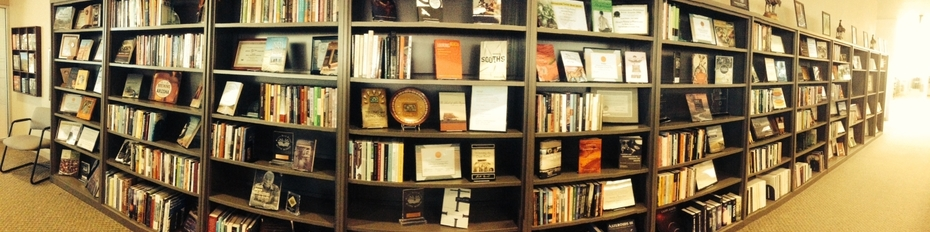 Photo of multiple book shelves displaying books published by the UA Press