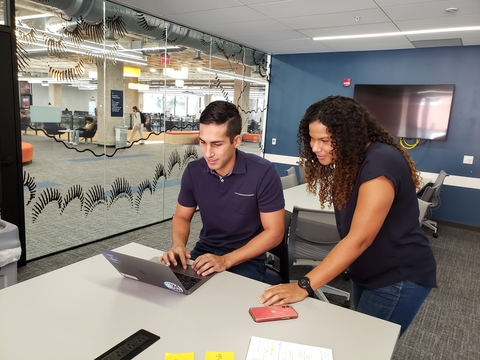 two people around a laptop working with a large monitor in the background and clear glass wall