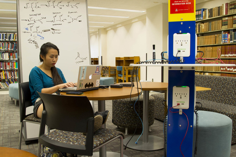 Student working on laptop at small table, near rolling whiteboard and charging station