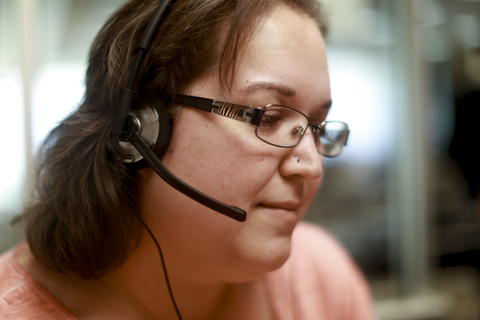 Photo of woman using headphones with microphone