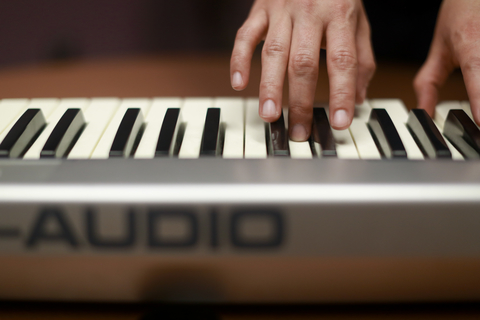 Photo of someone playing a MIDI keyboard