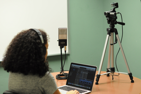 person using laptop and recording equipment