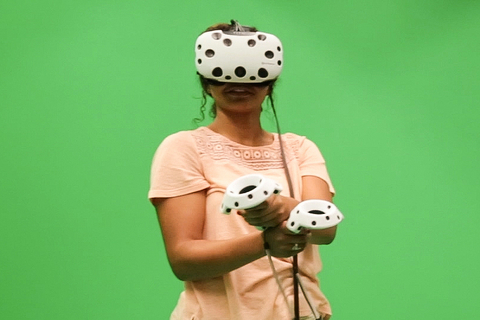 Student using a tethered VR device in front of a green screen