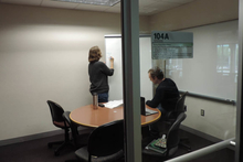 Instructor standing at rolling whiteboard, with a student seated at small meeting table